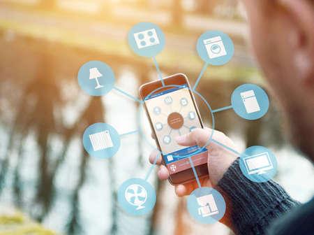 domotique: maison intelligente, la domotique, dispositif illustration avec ic�nes d'applications. Il est dans la nature tenant son smartphone avec l'application de maison intelligente Banque d'images
