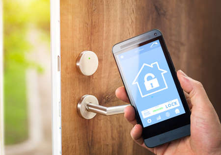 electronic device: smarthouse home automation device with app icons. Man uses his smartphone with smart home security app to unlock the door of his house.