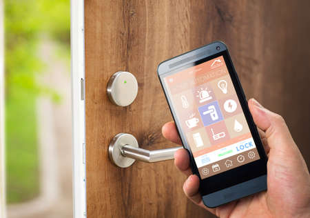smarthouse home automation device with app icons. Man uses his smartphone with smart home security app to unlock the door of his house.