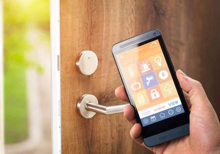 Smarthouse Hausautomationsgerät mit App-Symbole. Mann nutzt sein Smartphone mit Smart-Home-Sicherheits App, die Tür seines Hauses zu entsperren. Standard-Bild - 39578060
