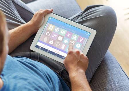 monitoreo: SmartHouse dispositivo de automatización del hogar con los iconos de aplicación. El hombre utiliza su tablet PC con la aplicación inteligente del hogar para controlar su casa. La nueva generación de Internet de las Cosas. Foto de archivo