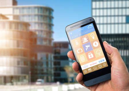 SmartHouse home automation apparaat met app iconen. De mens gebruikt zijn smartphone met smart home security app te bewaken en te beheersen zijn kantoor Stockfoto
