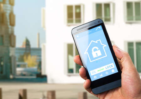 security monitor: smarthouse home automation device with app icons. Man uses his smartphone with smart home security app to unlock the door of his house.
