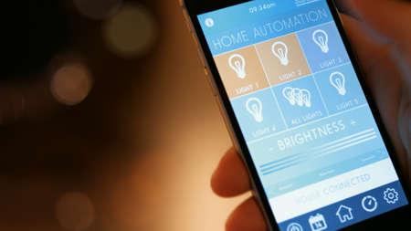 スマートな家、ホーム オートメーション、アプリのアイコンを持つデバイス。男は、彼の家の照明を制御するのにスマート ホーム アプリで彼のス