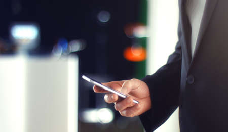 scrolling: Business Man using mobile phone smart phone in the office. Typing, reading, scrolling the touchscreen - blurry background with space for text.