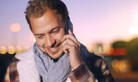 likeable: Handsome young man speaking on smart phone at autumn sunset in city. Using smartphone for a phone call, smiling happy wearing urban hipster outfit outdoors at dawn. Stock Photo