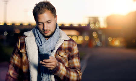 business man phone: Handsome young man sms texting using app on smart phone at autum Summer sunset in city. Using smartphone smiling happy wearing urban hipster outfit outdoors. Stock Photo