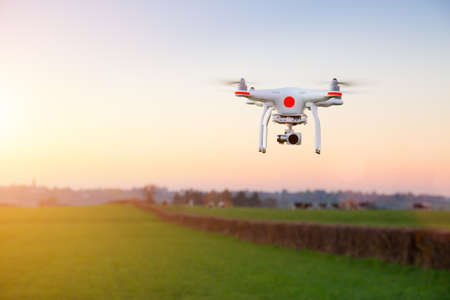 camera: Modern RC UAV Drone quadro copter with camera flying on a clear sunny sky sunset background with nice lens flare.