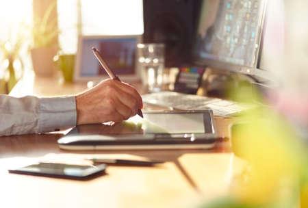 silencio: Diseñador gráfico trabaja con pantalla interactiva de la pluma, la tableta de dibujo digital y pluma en un ordenador. Smooth travelling con buen lensflare retroiluminada.