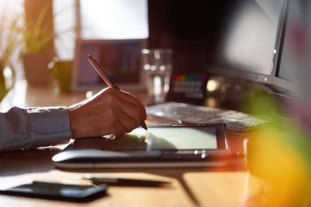 Diseñador gráfico trabaja con pantalla interactiva de la pluma, la tableta de dibujo digital y pluma en un ordenador. Smooth travelling con buen lensflare retroiluminada.
