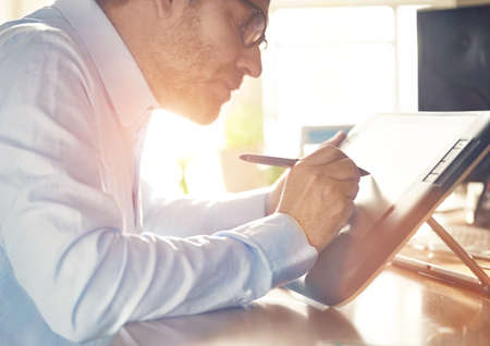 lensflare: Graphic Designer working with interactive pen display, digital Drawing tablet and Pen on a computer. Smooth tracking shot with nice backlit lensflare.