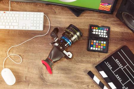 Desktop shot of a modern Digital Cinema Camera and clapboard on stylish wooden desktop Workplace Background Foto de archivo
