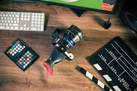 set: Desktop shot of a modern Digital Cinema Camera and clapboard on stylish wooden desktop Workplace Background Stock Photo