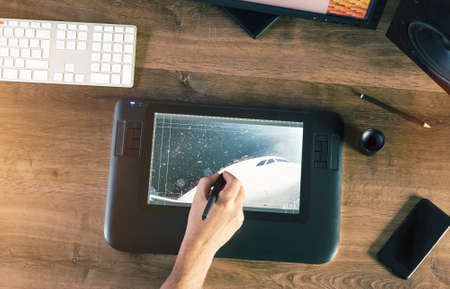 wacom: Graphic Designer working with interactive pen display, digital Drawing tablet and Pen on a computer on a wooden desktop. Above view shot