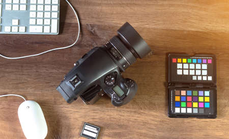 retouch: Top view of a modern desktop shot Digital Medium Format Camera with laptop on stylish Photo wooden desktop Workplace Background