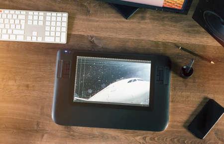 Graphic Designer travaillant avec écran à stylet interactif, tablette de dessin numérique et stylo sur un ordinateur sur un bureau en bois. Au-dessus de vue tir