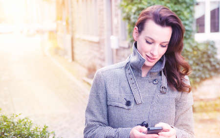 analogous: Businesswoman use her mobile phone outdoor in a historic village