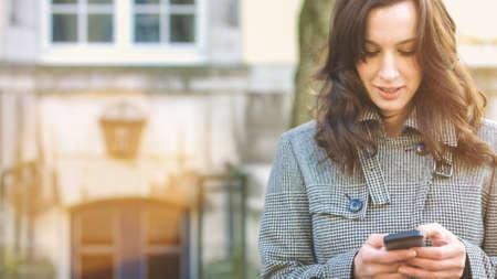 iluminado a contraluz: Empresaria usar su teléfono móvil al aire libre en un pueblo histórico