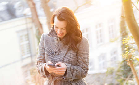 analogous: Businesswoman use her mobile phone outdoor in a historic village - sunny backlite