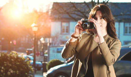 emulation: Attractive Tourist taking a photograph with vintage camera of Historic old village  town at sunset - Analog style film emulation