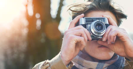 taking photograph: Attractive Tourist taking a photograph with vintage camera of Historic old village  town at sunset Stock Photo