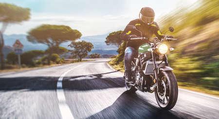 Motorrad auf der Straße fahren. Spaß haben die leere Straße auf einer Motorradtour Fahrt fahren. Exemplar für Ihren individuellen Text. Standard-Bild
