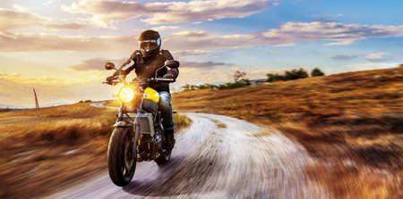 バイクに乗って道路に。オートバイ ツアー旅の空の道の運転の楽しみを有する。個々 のテキストの copyspace。 写真素材