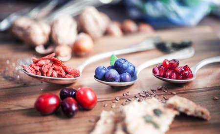 frutas secas: Súper alimento - Cucharas de varios súper alimentos en fondo de madera