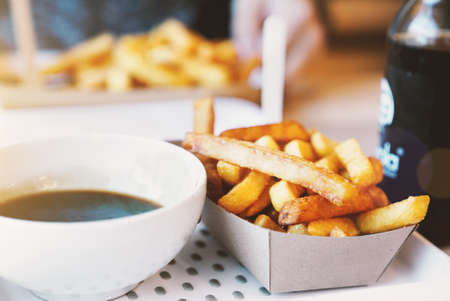 paper board: French fries on tracing paper on board on wooden table