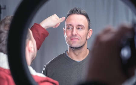 audition: makeup artist working on models face in shooting break on movie set location Stock Photo