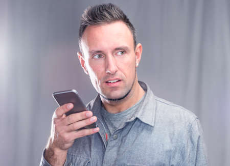 likeable: Handsome young man using his smart phone.  Using smartphone for voice message wearing urban hipster outfit  Stock Photo