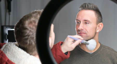 makeup artist working on models face in shooting break on movie set location Stock Photo