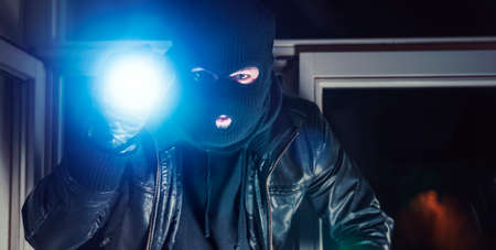 Masked burglar with torch and crowbar breaking and entering into a house - shot with dramatic motion Standard-Bild
