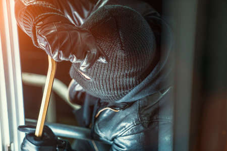 crowbar: Masked burglar with torch and crowbar breaking and entering into a house - shot with dramatic motion Stock Photo