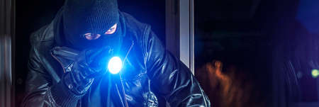 crowbar: Masked burglar with crowbar breaking and entering into a house - shot with dramatic motion