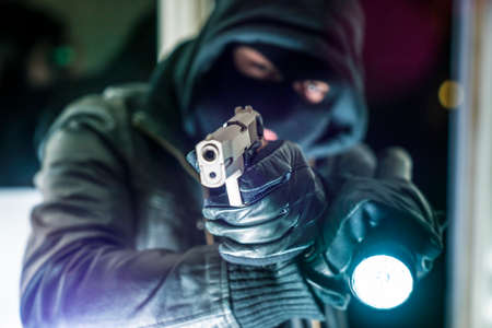 Masked burglar with pistol gun breaking and entering into a victim's home