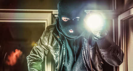 Masked burglar with torch and crowbar breaking and entering into a house - shot with dramatic motion Banque d'images