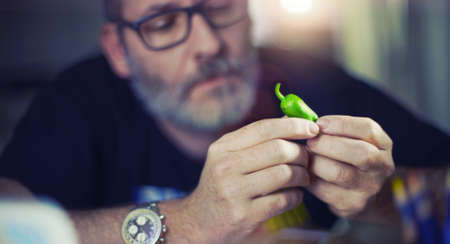 Creative designer looks at green pepper, hot chili pepper, searching for new ideas