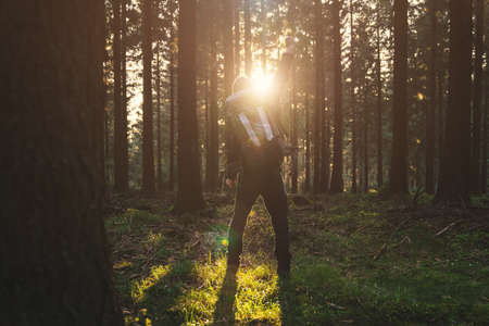 nature of sunlight: Young man stand in forrest and enjoys nature and sunlight