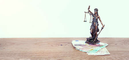 The Statue of Justice - lady justice or Iustitia  Justitia the Roman goddess of Justice on table with money for finance concept