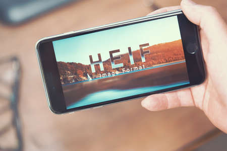 decoding: AACHEN, GERMANY - JUNE 22, 2017: HEIF Logo on  Apple iPone 7. HEIF is a new image compression used by apple in iOS 11 to reduce the storage on mobile devices, developed by the Moving Picture Experts Group (MPEG). Editorial