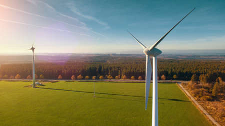 electric grid: Wind turbines and agricultural fields on a summer day - Energy Production with clean and Renewable Energy - aerial shot
