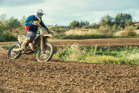 muddy: Arnoldsweiler, Germany, October 05,2017: Extreme Motocross MX Rider riding on dirt track on a sunny late summer day on public training session in preparation for motocross event. Editorial