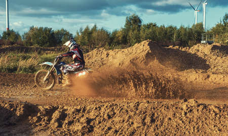 Extreme Motocross MX Rider riding on dirt track on a sunny late summer day on public training session in preparation for Motocross event Stock Photo