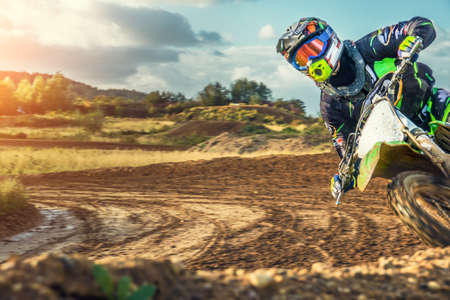Extreme Motocross MX Rider riding on dirt track on a sunny late summer day on public training session in preparation for Motocross event 스톡 콘텐츠