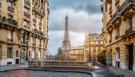 small paris street with view on the famous paris eiffel tower on a cloudy rainy day with some sunshine