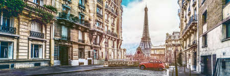 small paris street with view on the famous paris eifel tower on a cloudy rainy day with some sunshine - wide horizontal panorama Stock Photo
