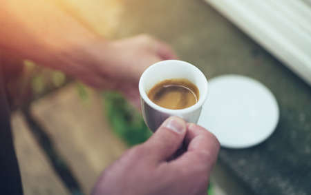 Young man hand holding a white cup of espresso on terrace in the morning Standard-Bild