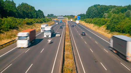 Veel vrachtwagens en auto's op een snelweg - transportconcept Stockfoto
