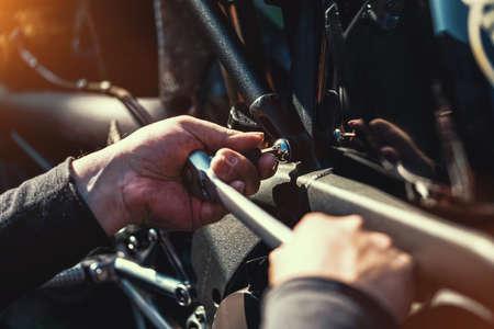 Mechanic working on Motocycle in mechanics garage. Repair service. authentic close-up shot 版權商用圖片
